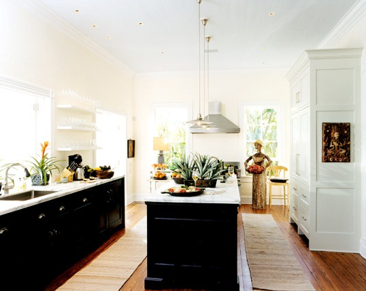 Kitchen with jet black lower cabinets, marble countertops, floating shelves instead of upper cabinets and pendant lights