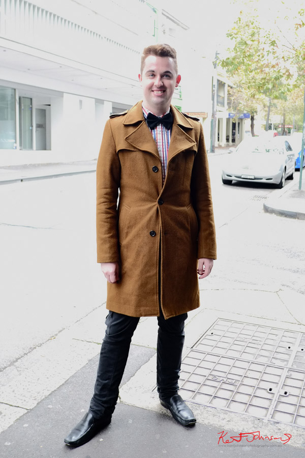 Men's winter style Sydney - Check shirt, bow tie, black slim fit cargo pants and caramel colour overcoat - Darlinghurst Rd Sydney. Photo by Kent Johnson.