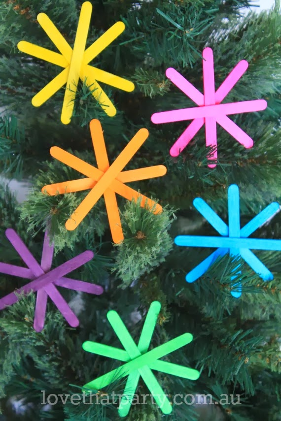 kids craft neon christmas decorations made with popsicle sticks on tree