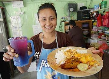 Siti Muzalifah showing the lunch menu of rice with curried chicken and vegetables for RM4 at her restaurant on Gat Lebuh China.
