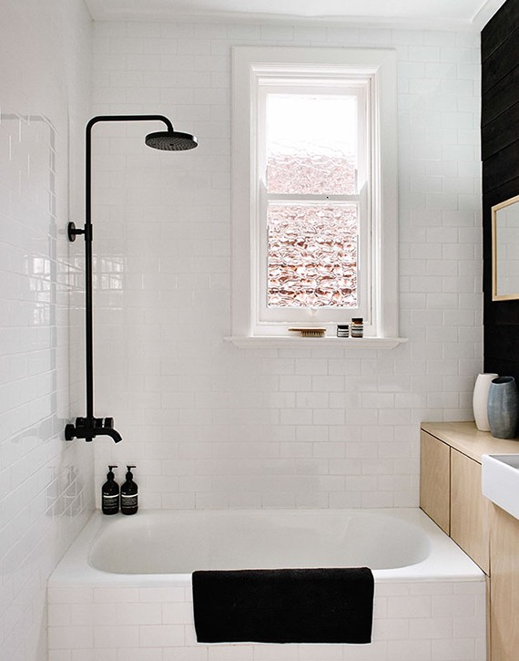 Black fixtures in the bathroom | Black shower and wall contrast with wooden cabinet and white tiles. Design by Fran Woodall, photo by Terence Chin via Sharedesign.