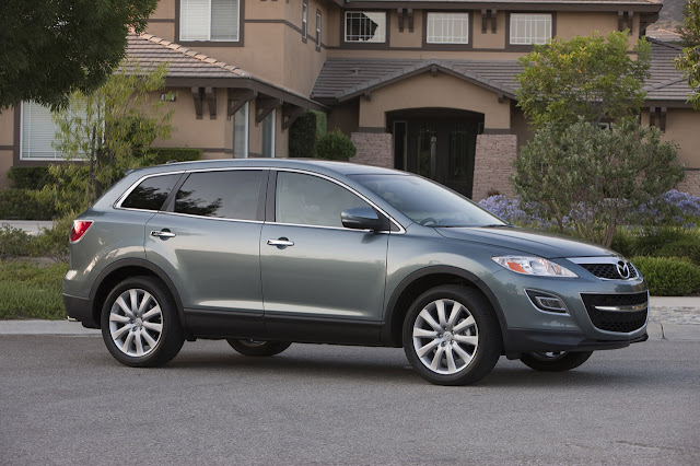 Front 3/4 view of silver 2011 Mazda CX-9 parked in front of home