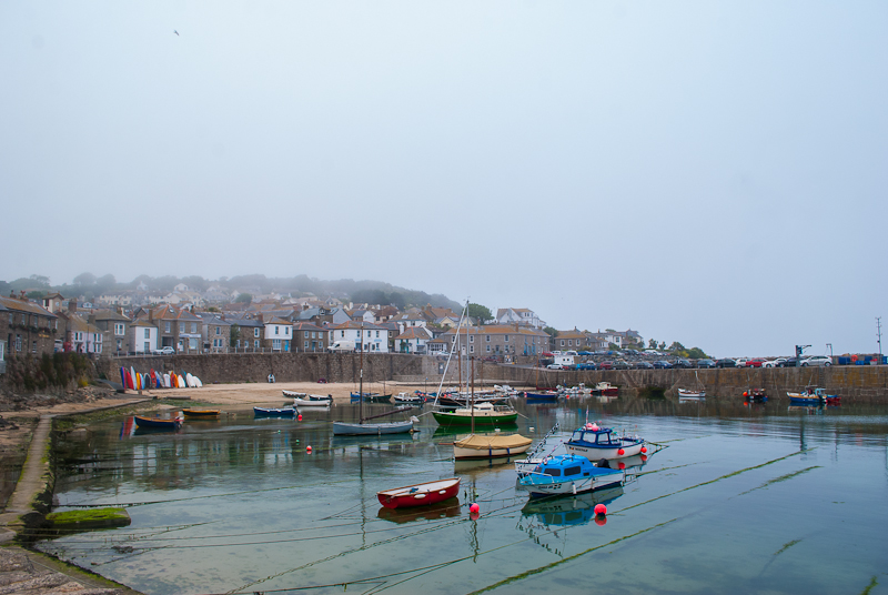 Inner harbour with small boats in mousehole cornwall, england. Clear waters and foggy skies