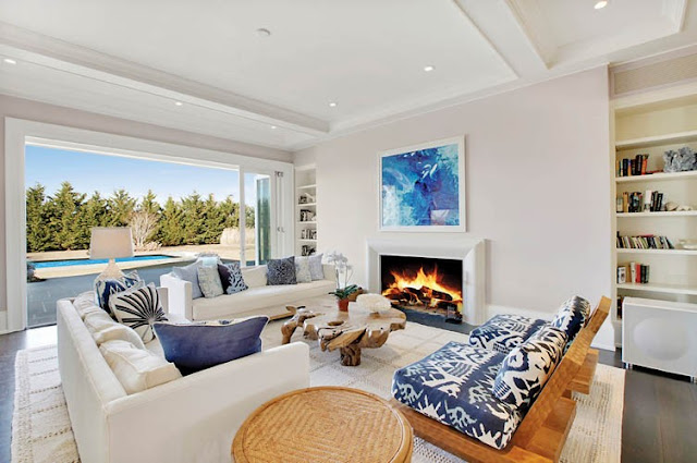 living room white high ceilings and walls, a large window overlooking the pool, a fireplace, built in bookshelf, dark wood floor, a natural trunk coffee table, two sofas and two outdoor wooden arm chairs with blue and white cushions