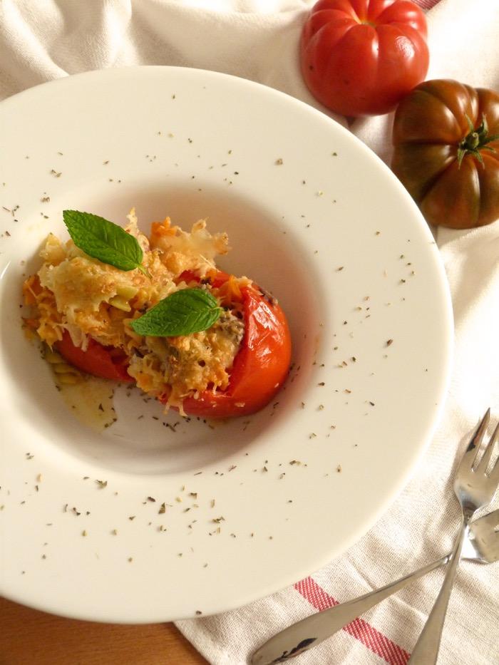 tomates asados rellenos de pasta y achoa. Gratinados