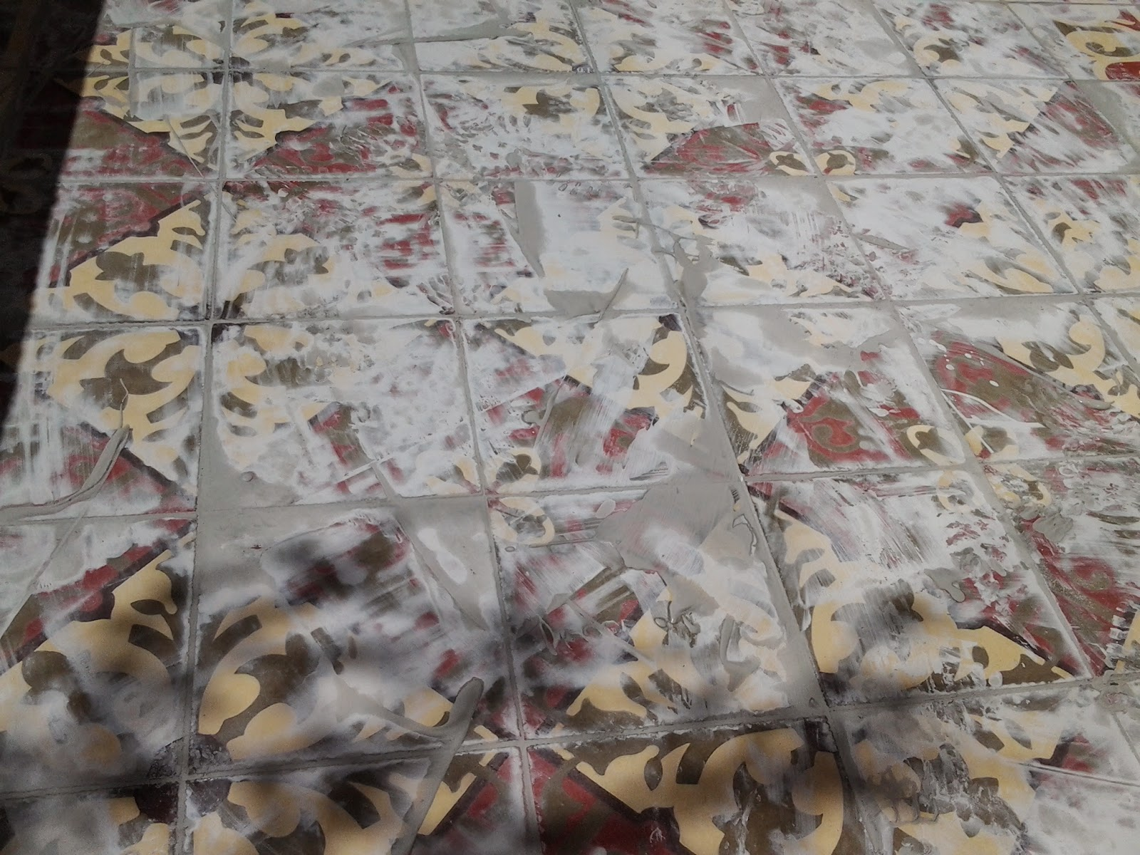 Grout being applied to patterned cement tiles  - a messy job!