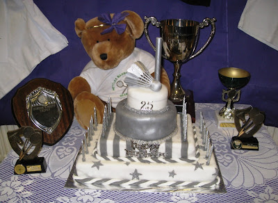 Bear mascot, trophies and 25th anniversary cake featuring silver shuttlecocks
