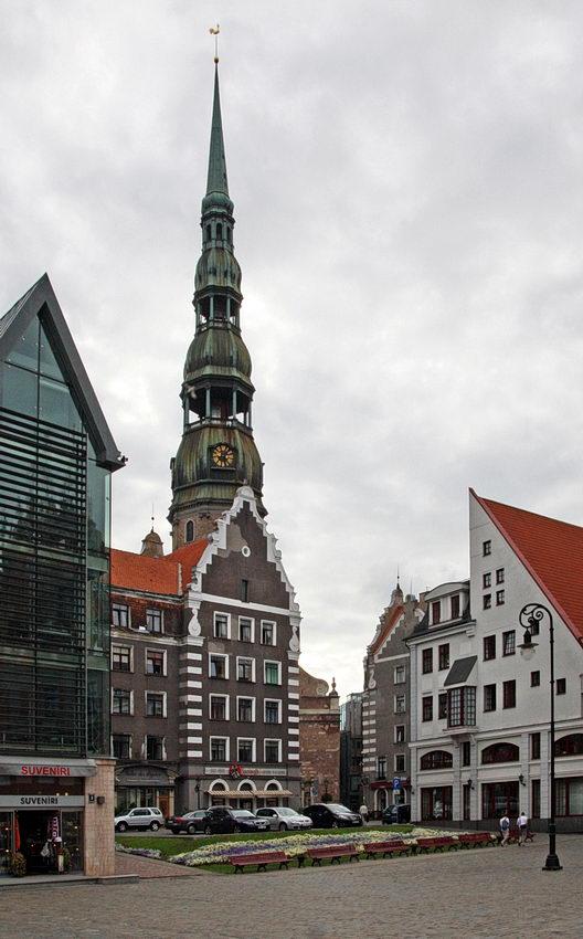 Foto duma praça com a torre da igreja por detrás