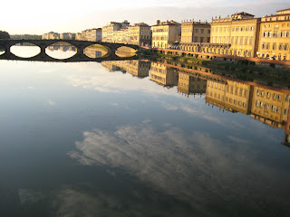 A photo showing a bridge and clouds reflected in the Arno River in Florence, Italy.