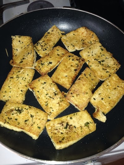 Tofu slices with seasoning after flipping in frying pan