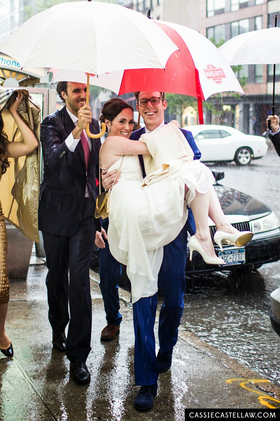 Bridal party with umbrellas sheilding groom carrying bride in the pouring rain. NYC Lifestyle wedding photography by Cassie Castellaw. www.cassiecastellaw.com
