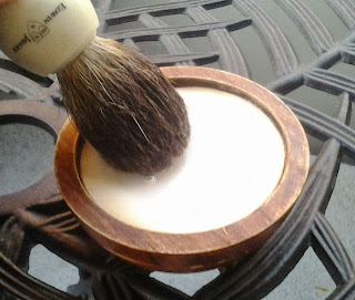 Applying warm water to a shaving soap with a pure badger shaving brush