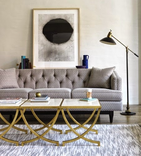 sofa gris capitone y mesas laton