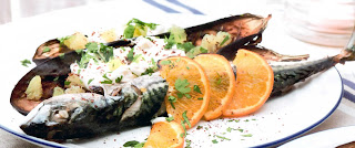 Barbecued mackerel served with baked aubergines and orange garnish.