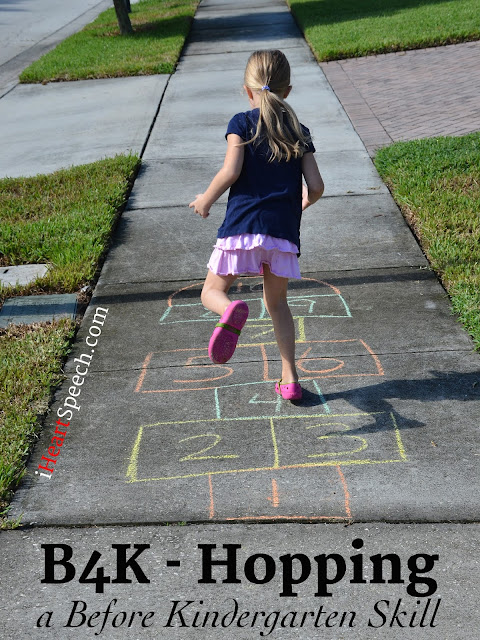 kindergarten child hopping on a hopscotch board