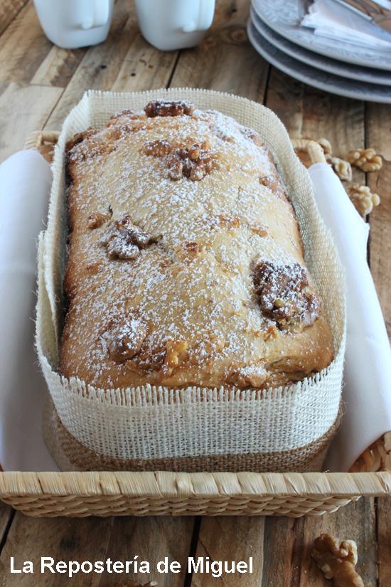 Pan entero visto desde una perpectiva frontal en el que se aprecia toda la parte superior del pan , con todas las nueces encima y el azúcar glass espolvoreado sobre él.