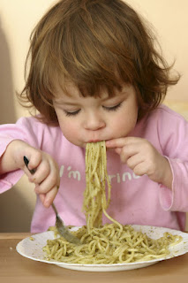 young child eating pasta with pesto sauce