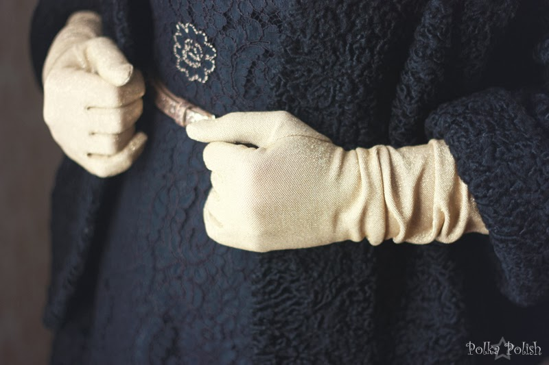 Gold lame evening gloves with a black cocktail dress and coat.