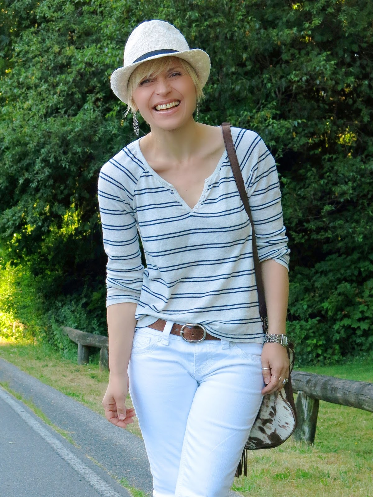 styling white jeans with a striped henley top and a fedora