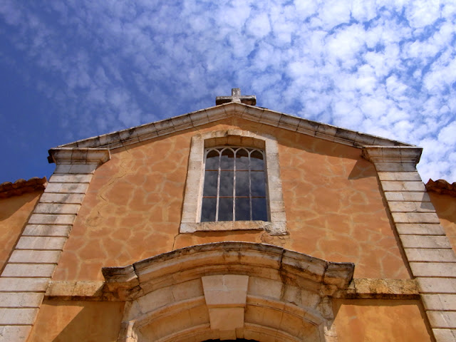 Kirche in Roussillon, Frankreich in der Provence mit blauem Himmel und ein paar fluffigen Wölkchen am Himmel