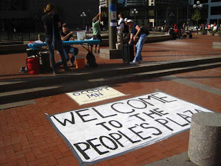 Occupy Minnesota welcome table with large sign that says welcome to the people's plaza