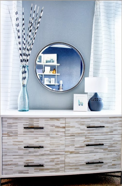 attractive round mirror and contemporary table decoration mounted on modern drawer