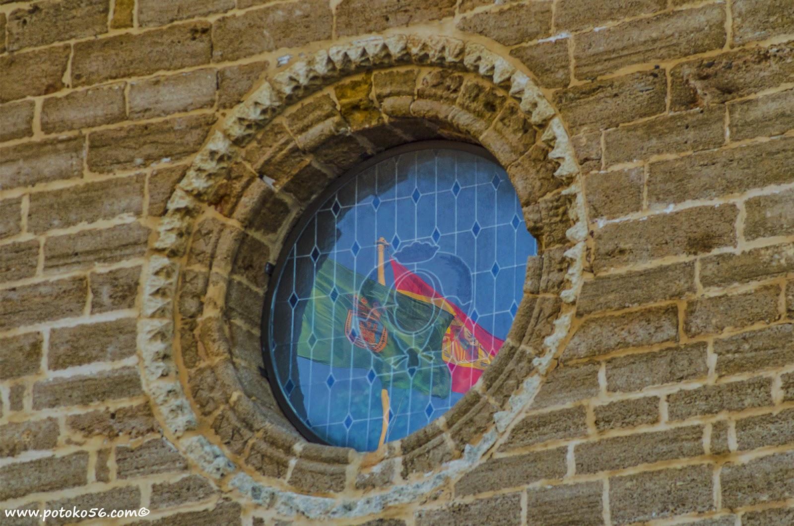 Reflejos de las banderas en la vidriera de la Parroquia de La O en Rota