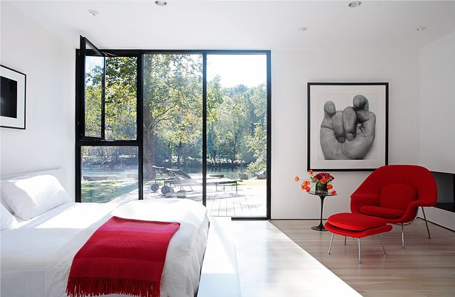 modern bedroom with a encasement window with black trim, wood floor, a red chair and a red throw on a white bed
