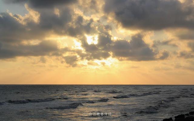 夕陽躲在雲層厚,卻形成耶穌光,束束光芒照耀在海面上,染上一層金黃。