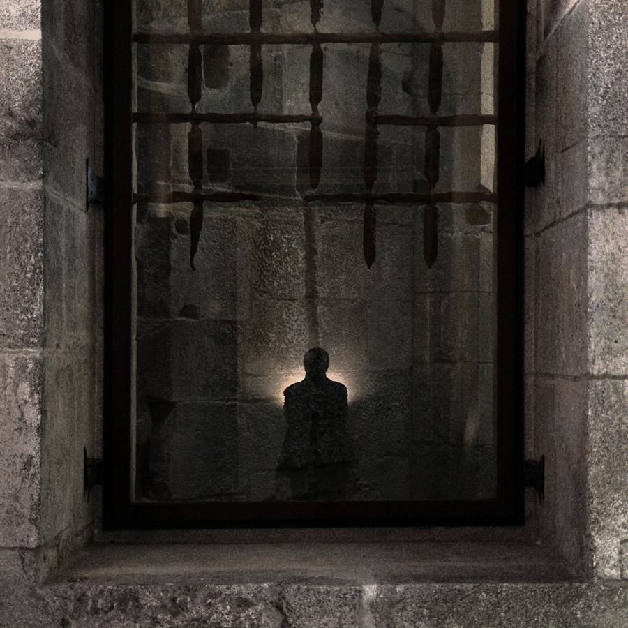 Auto-retrato pelo reflexo num vidro de uma passagem. Visíveis as ruínas das grades de ferro da prisão