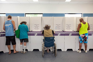 image shot from behind showing 4 men, one man a wheelchair user, voting at a polling place.