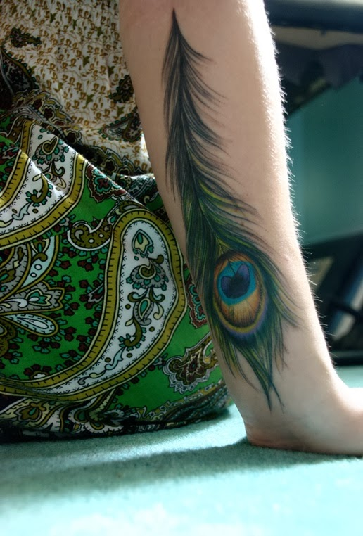 Peacock feather tattoos on women arm