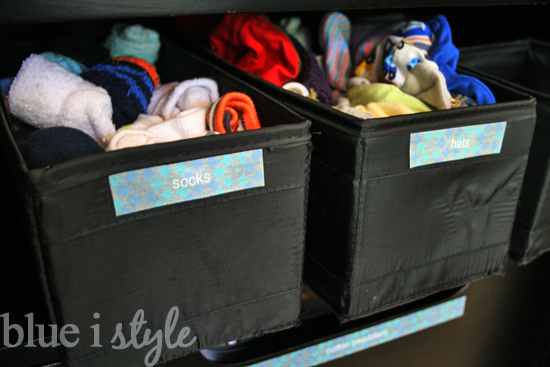 baskets on armoire shelf for baby clothes socks and supplies