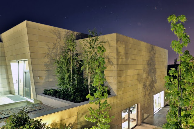 Stone facade of The Memory House by A-Cero Architects at night