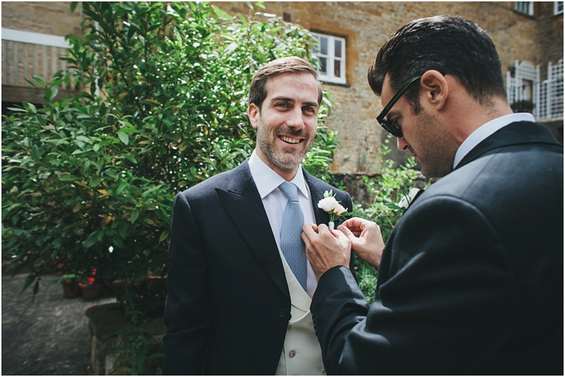 Groom with usher putting on buttonhole