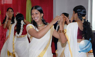 Kerala girls dancing and singing during Onam celebrations.