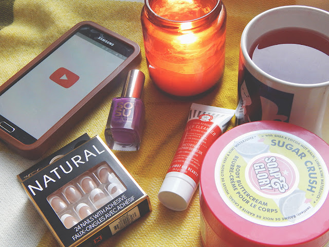 Flat lay photo with a phone, fake nails, nail polish, face mask, mug of tea, bodybutter and a candle