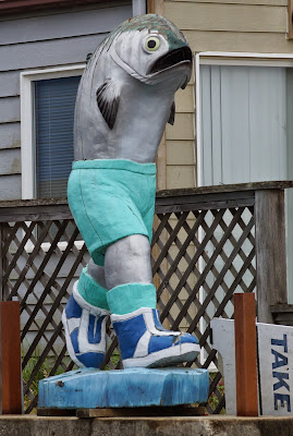 carving of a walking salmon in shorts and sneakers