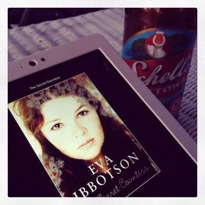 A white Kobo with The Secret Countess's cover on its screen lays at an angle to a bottle of beer. The cover features a close-in photograph of a young white woman with brown hair. The beer's label has a goose on it.