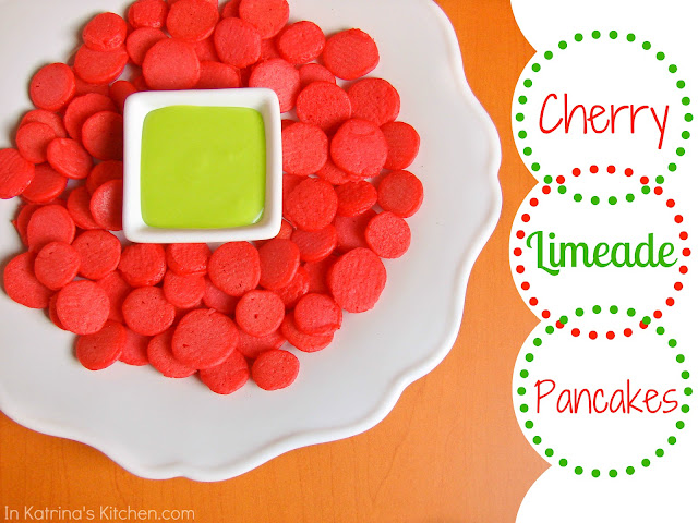 Lots of tiny cherry pancakes surrounding a small square bowl containing green dip, on orange background. Text overlay reads cherry limeade pancakes.