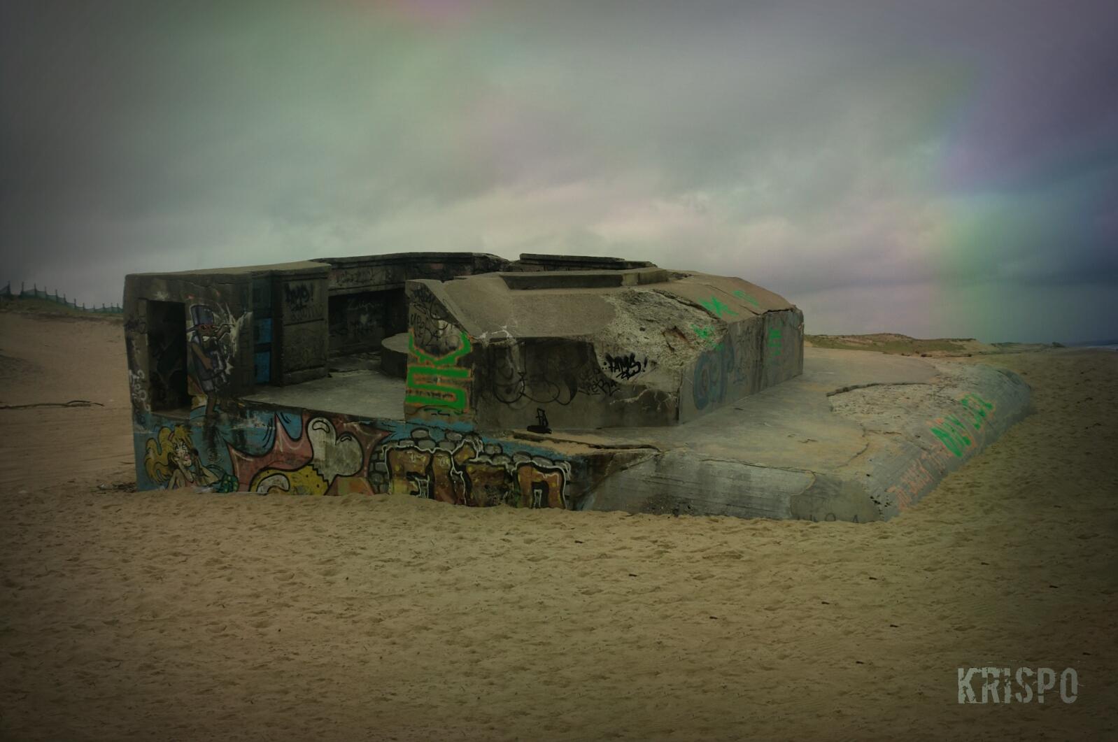 bunker semienterrado pintado con graffitis en playa de las landas