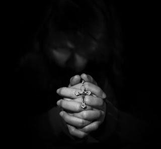 [pregare per le proprie colpe con una croce in mano]