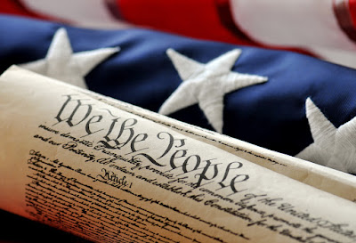 Image of the constitution in front of American flag