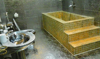 Holiday in Vietnam: Stylish golden tiled bath. Shame the hot water system couldn't supply a hot bath.