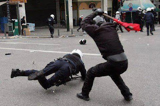 funniest picture of police: demonstrator hits policeman with stick