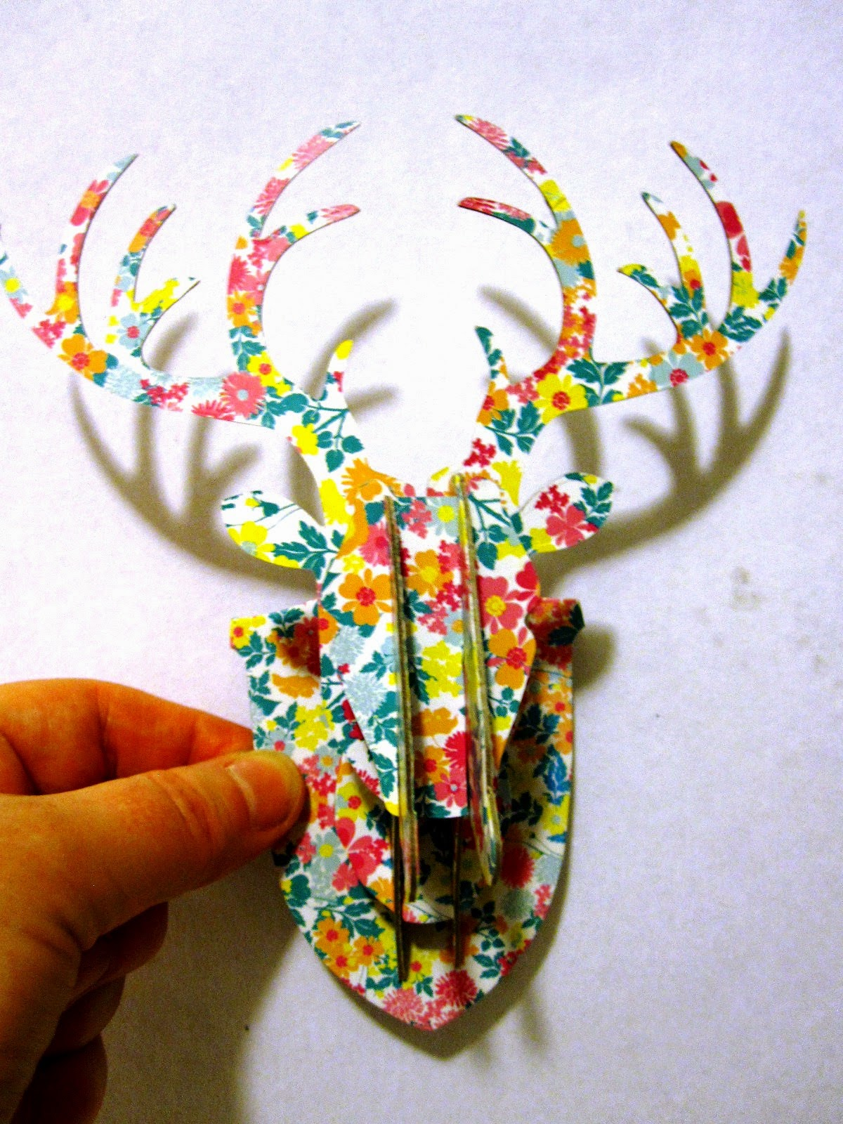 A hand holding up a miniature cardboard stag head, printed with a flower pattern.