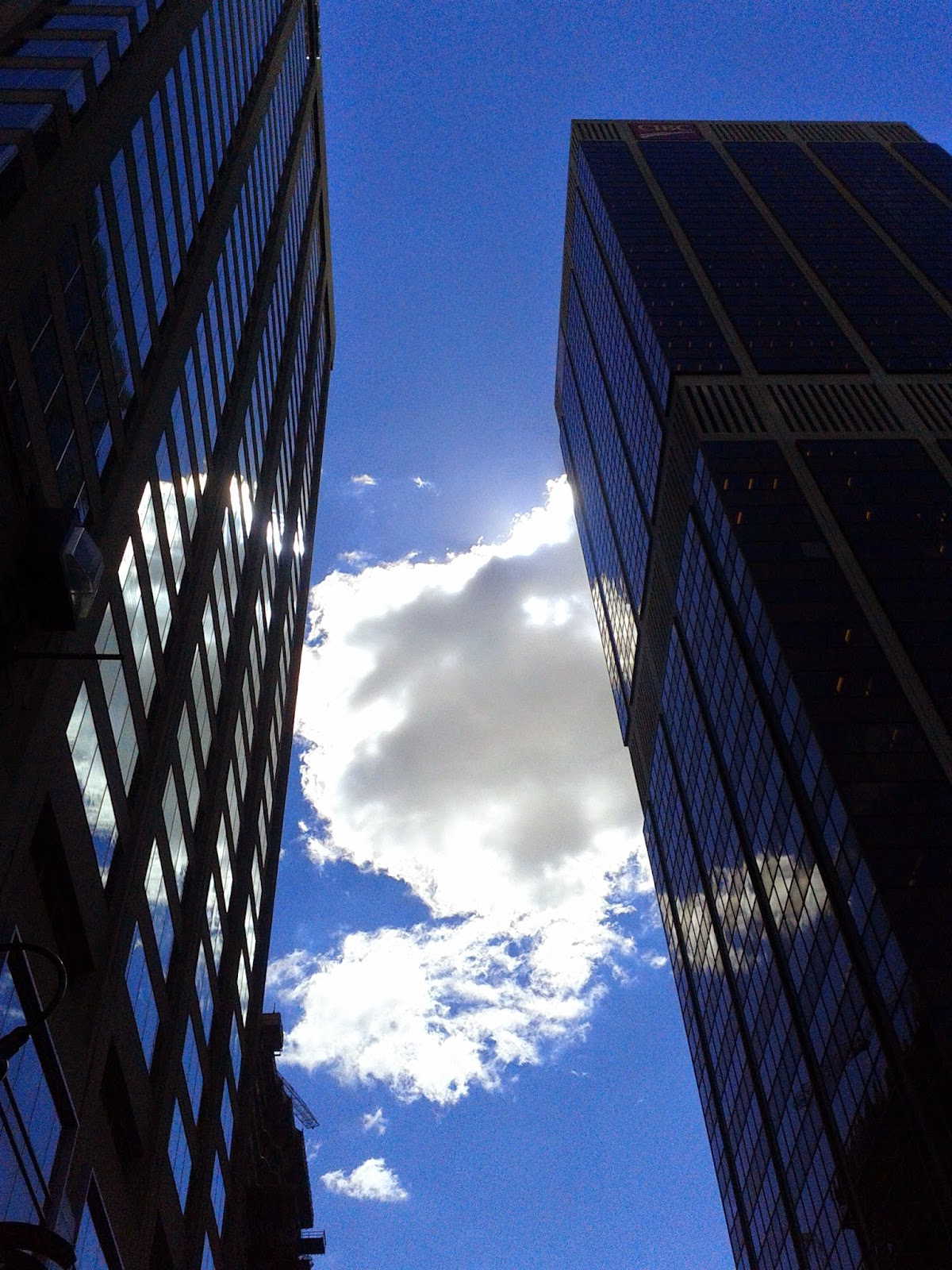 Stock photo: Blue sky and clouds in between buildings towers