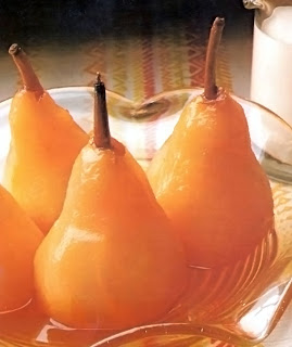 Pears poached in cider in a pressure cooker served upright in a glass dish.