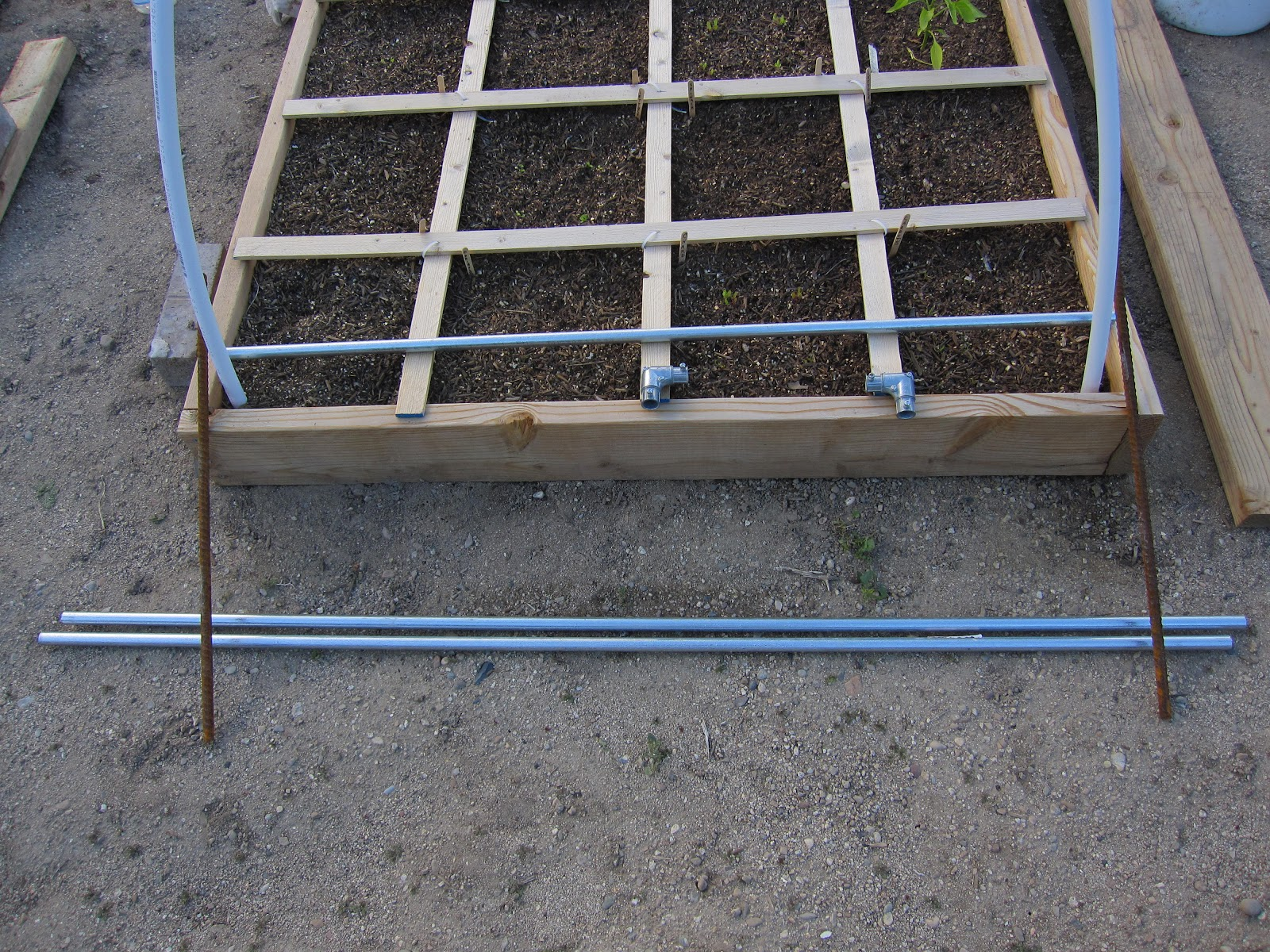 in my league building a square foot garden trellis rebar at each corner 2 five foot lengths of pipe shown on the ground connectors and four foot length of pipe resting on the box