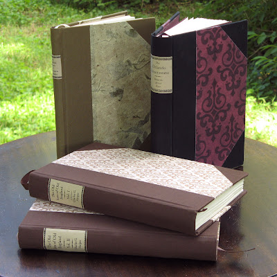 Four handmade hardcover books, printed from public-domain ebooks